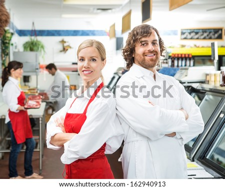 Portrait of confident butchers standing arms crossed in store - stock photo