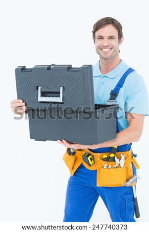 Portrait of confident carpenter opening tool box against white background - stock photo