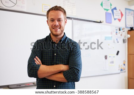 Portrait of confident Caucasian male teacher in classroom - stock photo