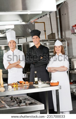 Portrait of confident chefs standing with arms crossed in industrial kitchen - stock photo