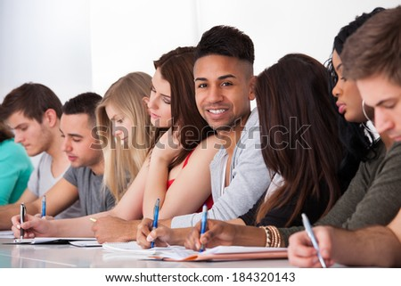 Portrait of confident college student sitting with classmates writing at desk in classroom - stock photo