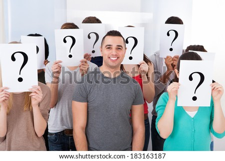 Portrait of confident college student surrounded by classmates holding question mark signs in classroom - stock photo