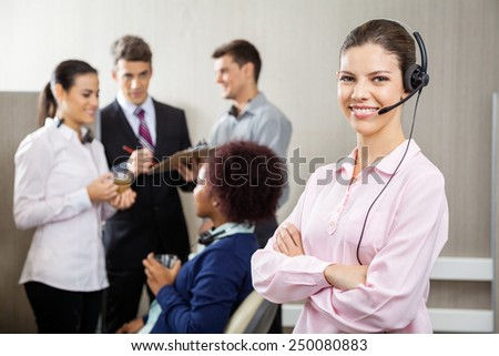 Portrait of confident customer service representative standing arms crossed at office while team discussing in background - stock photo
