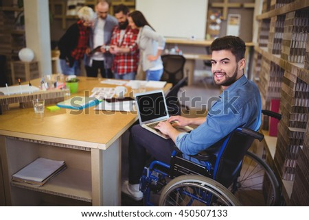 Portrait of confident disabled businessman using laptop at desk in creative office - stock photo