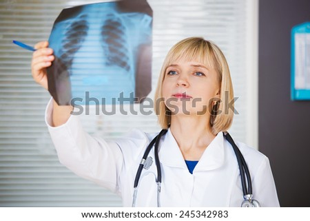Portrait of confident doctor looking at xray. - stock photo