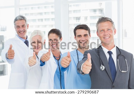 Portrait of confident doctors in row thumbs up in the hospital - stock photo