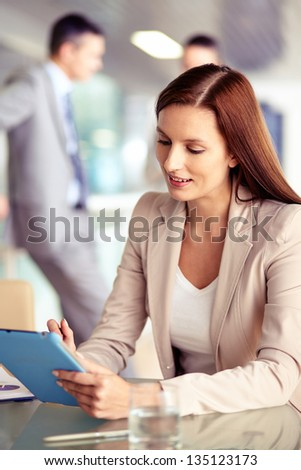 Portrait of confident employee working with touchpad on background of working colleagues - stock photo
