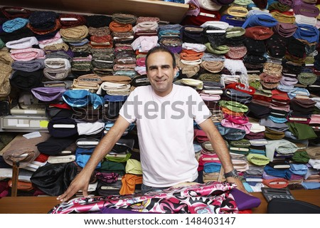Portrait of confident fabric store owner standing at counter - stock photo