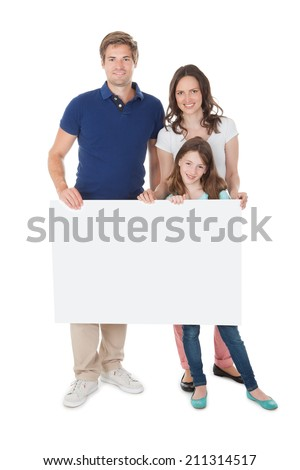 Portrait of confident family holding blank billboard over white background - stock photo