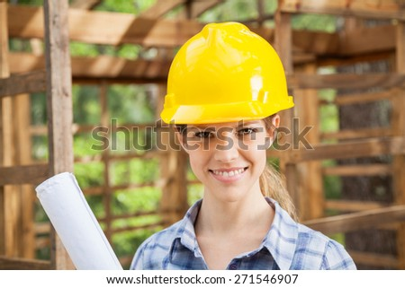 Portrait of confident female architect wearing yellow hardhat in wooden cabin at construction site - stock photo