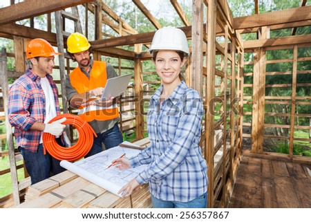 Portrait of confident female architect working on blueprint with male colleagues using laptop in incomplete wooden cabin at site - stock photo