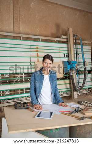 Portrait of confident female carpenter standing at table against vertical panel saw - stock photo