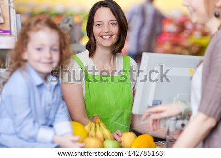 Portrait of confident female cashier smiling with mother and daughter in foreground at supermarket - stock photo