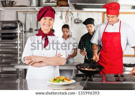 Portrait of confident female chef with colleagues cooking in industrial kitchen - stock photo