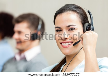 Portrait of confident female customer service executive with colleagues in background at call center - stock photo