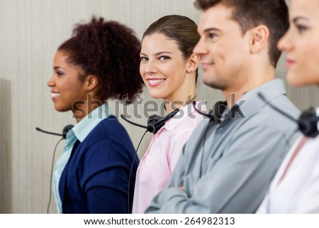 Portrait of confident female customer service representative standing with colleague at call center - stock photo