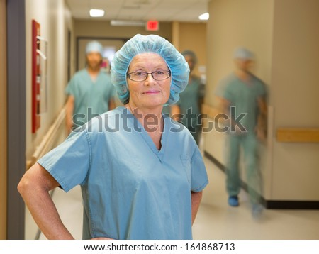 Portrait of confident female doctor with team walking in hospital corridor - stock photo