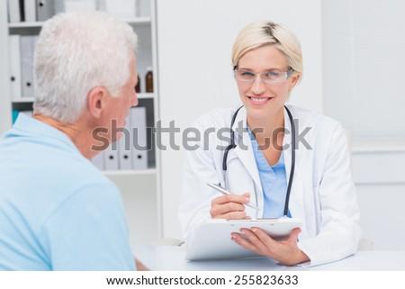 Portrait of confident female doctor writing prescription for senior man in clinic - stock photo