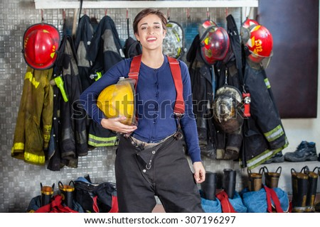 Portrait of confident female firefighter holding helmet while standing at fire station - stock photo