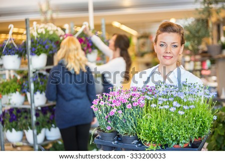 Portrait of confident female florist carrying flower plants with colleague assisting customer in background at shop - stock photo