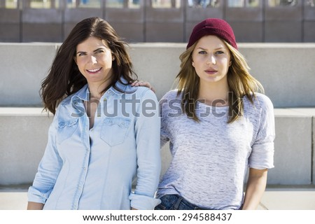 Portrait of confident female friends in casuals standing at beach - stock photo