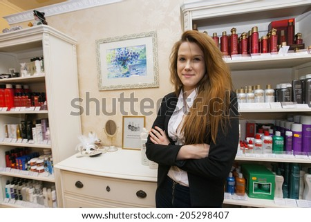 Portrait of confident female hairstylist in beauty salon - stock photo