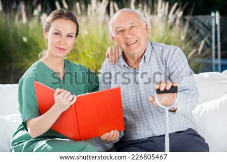 Portrait of confident female nurse and senior man with book at nursing home - stock photo