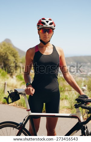 Portrait of confident female triathlete standing with her bicycle on country road. Fitness woman in sports wear standing with her bike. Female cyclist practicing for triathlon. - stock photo