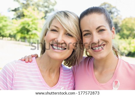 Portrait of confident female volunteers participating in breast cancer awareness at park - stock photo
