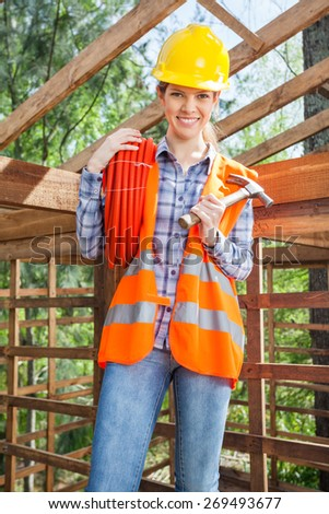 Portrait of confident female worker holding pipe and hammer in wooden cabin at construction site - stock photo