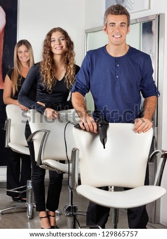 Portrait of confident hairdressers with hairdryer and scissors in salon - stock photo