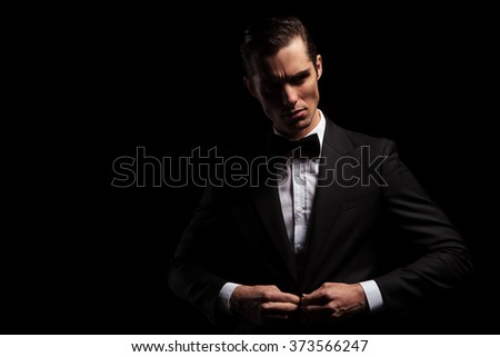 portrait of confident handsome man in black suit with bowtie posing in dark studio background while closing his jacket  - stock photo