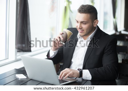 Portrait of confident happy smiling young business man sitting with glass of drink in coffee shop interior. Successful attractive caucasian man using notebook computer, typing in cafe. Indoors - stock photo