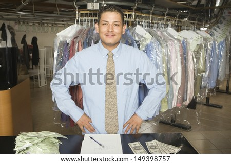 Portrait of confident laundry owner with receipts; notepad and banknotes standing at counter - stock photo