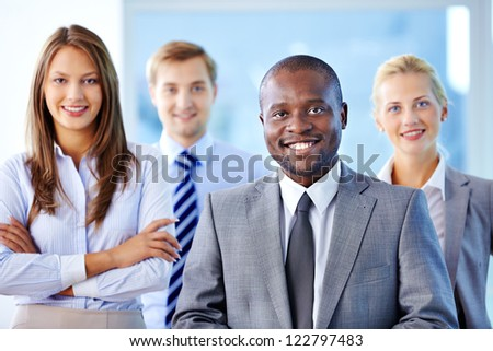 Portrait of confident leader looking at camera with three partners behind - stock photo