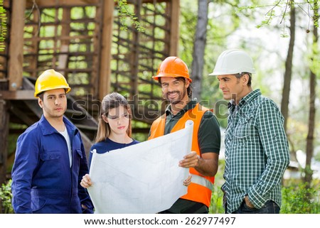 Portrait of confident male architects with colleagues analyzing blueprint at construction site - stock photo