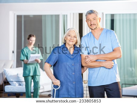 Portrait of confident male caretaker and disabled senior woman with female nurse in background at nursing home yard - stock photo