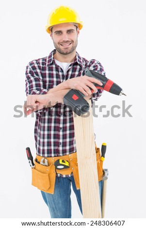 Portrait of confident male carpenter with drill machine and plank on white background - stock photo