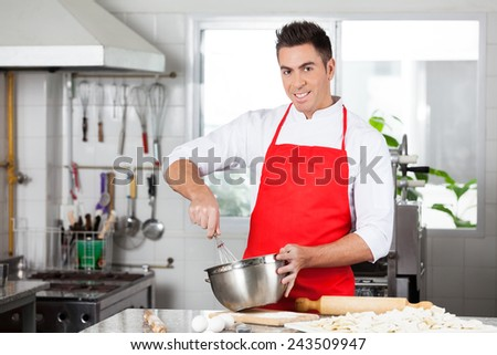 Portrait of confident male chef using eggbeater to prepare ravioli pasta in commercial kitchen - stock photo