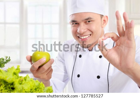 Portrait of confident male chef with apple - stock photo