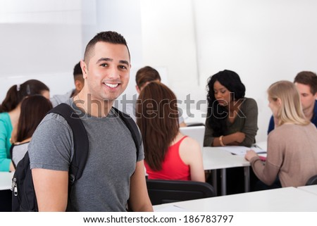 Portrait of confident male college student carrying backpack with classmates in background - stock photo
