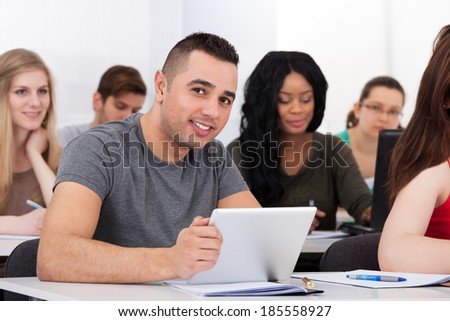 Portrait of confident male college student holding digital tablet at desk in classroom - stock photo