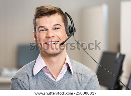 Portrait of confident male customer service representative wearing headset while smiling in office - stock photo