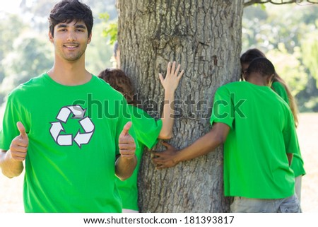 Portrait of confident male environmentalist gesturing thumbs up with friends hugging tree in background - stock photo