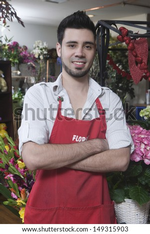 Portrait of confident male florist standing arms crossed in flower shop - stock photo