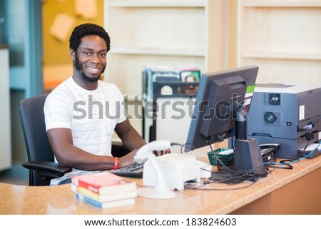 Portrait of confident male librarian working at desk in library - stock photo