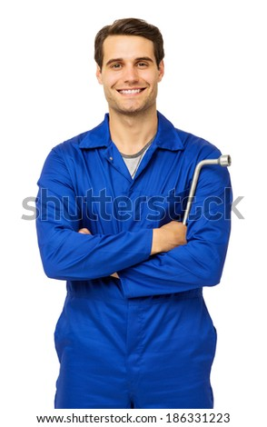 Portrait of confident male mechanic standing with arms crossed holding wrench over white background. Vertical shot. - stock photo