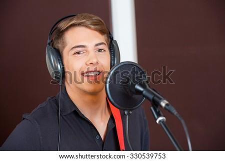 Portrait of confident male singer performing in recording studio - stock photo