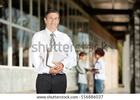 Portrait of confident male teacher holding books while standing on college campus - stock photo
