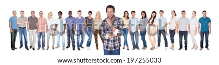 Portrait of confident man in casuals with friends standing against white background - stock photo